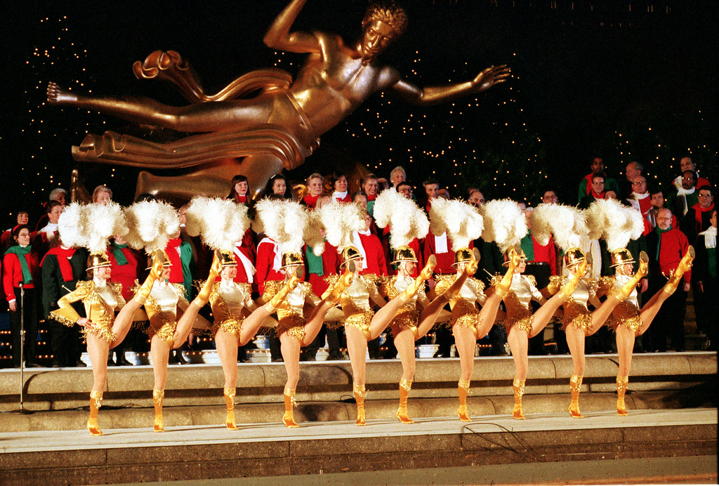 . The Radio City Rockettes perform in front of the Prometheus statue at the ice skating rink at Rockefeller Center during the 61st Rockefeller Christmas Tree lighting in New York City, Thursday, Dec. 2, 1993.  (AP Photo/Ed Bailey)