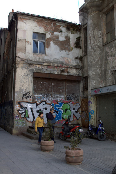 Scooters, people, building, graffiti.