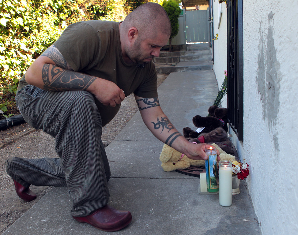 . Jason Redwine, of Oakland, drops off candles outside the home where an 8-year-old girl was killed in a shooting that also injured two other children and an adult along Wilson Avenue in Oakland, Calif., on Thursday, July 18, 2013. Redwine lives in the neighborhood. (Anda Chu/Bay Area News Group)