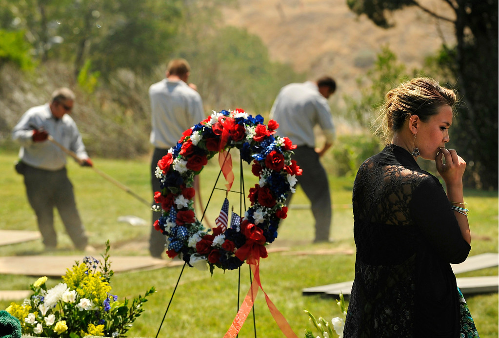 . Chantel Blunk, wife of Jonathan Blunk, waits as cemetery workers lower her husband\'s casket into the ground. She refused to leave Mountain View Cemetery until her husband was completely buried, Friday, August 03, 2012, after a service in Reno, Nevada.