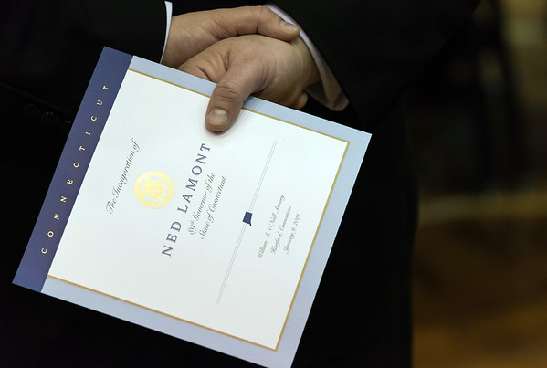 01/09/19 Wesley Bunnell | Staff A guest holds a handout from inauguration ceremony for Governor Ned Lamont.