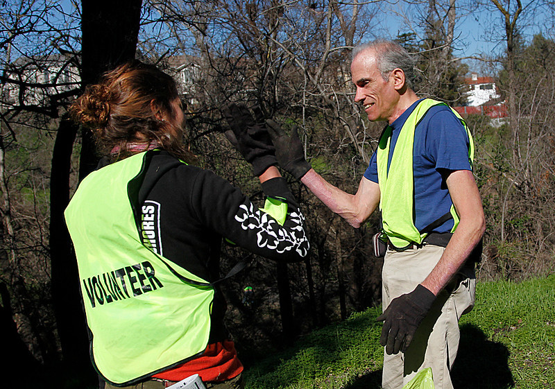 . Richard Gehrs, right, gives a high five to Rachel Kippen of Save Our Shores, after carrying bags of trash out of Coyote Creek during a clean-up near the Highway 280 overpass and Selma Olinder Park, in San Jose, Calif. on Saturday, Feb. 9, 2013.   (LiPo Ching/Staff)
