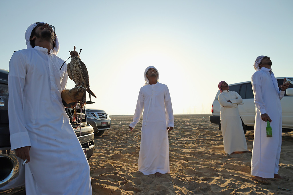 . Emirati men watch as a small helicopter drone takes a lure consisting of a bundle of feathers up before letting their Falcons catch it on February 3, 2015 in Abu Dhabi, United Arab Emirates. (Photo by Dan Kitwood/Getty Images)