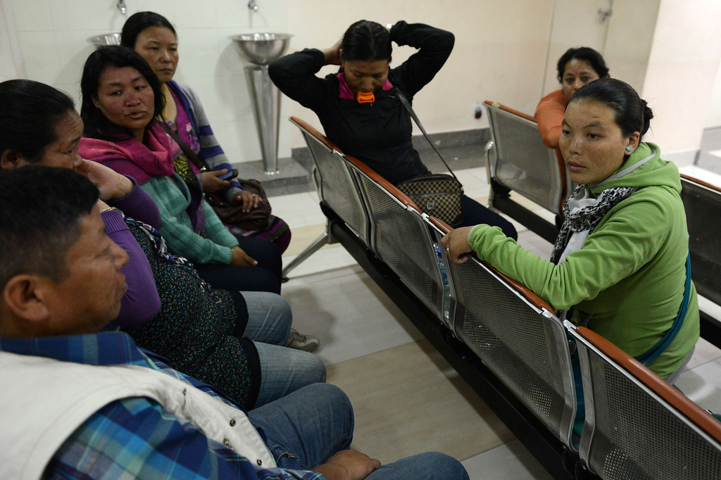 . Fhurbu Sherpa, (R), wife of Nepalese mountaineer Dawa Tashi Sherpa who survived an avalanche on Mount Everest, waits with family members at the Grandi International Hospital in Kathmandu on April 18, 2014.  At least 12 Nepalese guides preparing routes up Mount Everest for commercial climbers were killed by an avalanche in the most deadly mountaineering accident ever on the world\'s highest peak, officials and rescuers say.The men were among a large party of Sherpas carrying tents, food and ropes who headed out in bright sunshine in an early morning expedition ahead of the main climbing season starting later this month.  PRAKASH MATHEMA/AFP/Getty Images