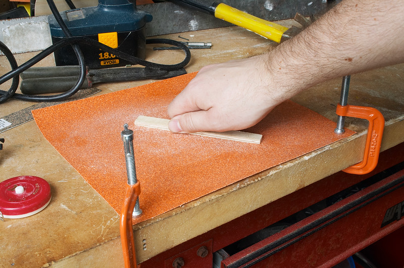 "Sanding down a 1/4"" piece of plywood to the right thickness for holding scotch tape at the film plane for collimation"