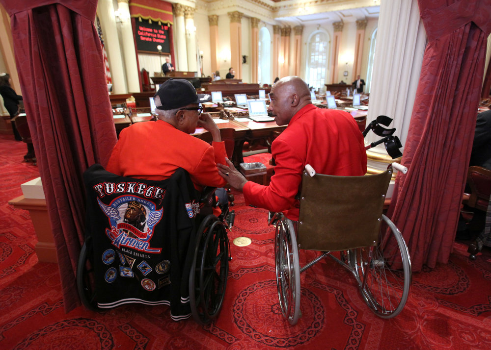 ". George W. Porter, left, and Michael Harrison, right, members of the George S. ""Spanky\"" Roberts Chapter of the Tuskegee Airmen, Inc., wait to be introduced to the state Senate during ceremonies honoring the Tuskegee Airmen during Black History Month at the Capitol in Sacramento, Calif., Tuesday, Feb. 21, 2012.  Both houses  of the Legislature honored the Tuskegee Airmen who were part of an Army Air Corps program to train African Americans to fly and provide support for combat aircraft during World War II. (AP Photo/Rich Pedroncelli)"
