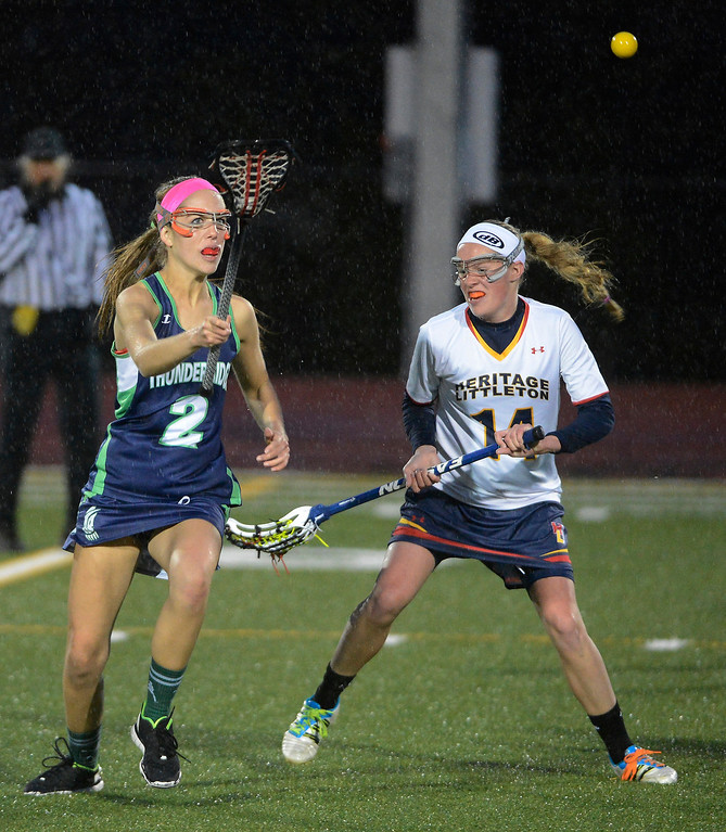 . LITTLETON, CO - MAY 8: Lindsey Givin, left, ThunderRidge High School, tries to get control of the ball against Michelle Johnson, Heritage/Littleton during the second half of play at Littleton Public Schools Stadium during the first round of the 2013 Colorado Girls State Lacrosse Championships May 8, 2013. ThunderRidge won 8-5. (Photo By Andy Cross/The Denver Post)