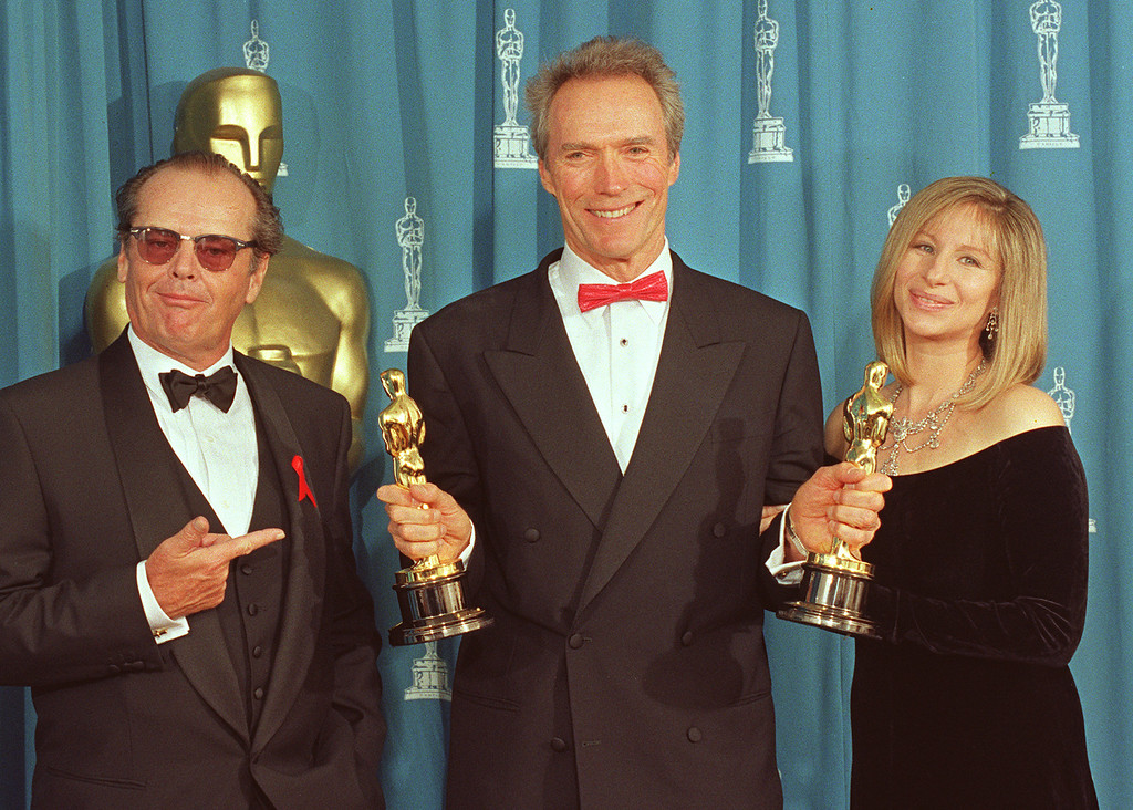 ". US actor Clint Eastwood (C) holds up his two Oscars at the 65th Annual Academy Awards 29 March 1993 that he won for Best Director and Best Picture for ""Unforgiven\"". Eastwood poses with presenters, actor Jack Nicholson (L) and entertainer Barbra Streisand.  (SCOTT FLYNN/AFP/Getty Images)"