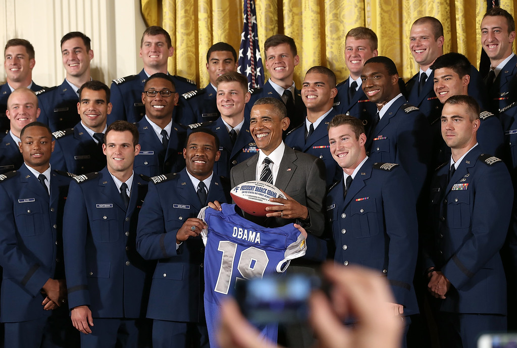 . President Barack Obama is presented with a football and a jersey after presenting the Commander-in-Chief trophy to the United States Air Force Academy football team in the East Room of the White House May 7, 2015 in Washington, DC. The Commander-in-Chief trophy is awarded each year to the winner of the American football series featuring the U.S. Naval Academy, U.S. Air Force Academy and U.S. Military Academy. (Photo by Win McNamee/Getty Images)