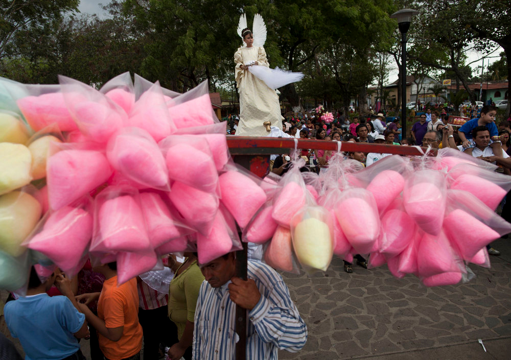 . A girl wearing an angel costume is carried during a Good Friday procession in Masaya, Nicaragua, Friday, March 29, 2013. Holy Week commemorates the last week of the earthly life of Jesus Christ culminating in his crucifixion on Good Friday and his resurrection on Easter Sunday. (AP Photo/Esteban Felix)