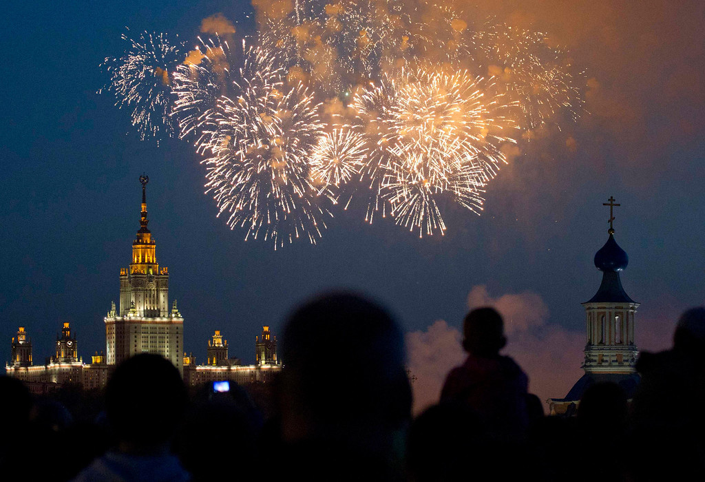 . Spectators watch as fireworks explode in the sky above an Orthodox church with Moscow State University main building (L) in the background during a display as part of celebrations for Victory Day in Moscow May 9, 2013.  Russia commemorates the 68th anniversary of the Soviet Union\'s victory over Nazi Germany on May 9. REUTERS/Maxim Shemetov