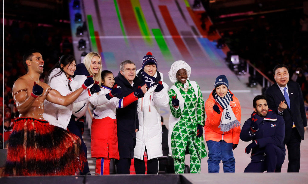 . Athletes from various nations including Pita Taufatofua, of Tonga, at left, United States\' Lindsey Vonn, third from left, and Thomas Bach, president of the International Olympic Committee, fifth from left, pose for photos during the closing ceremony of the 2018 Winter Olympics in Pyeongchang, South Korea, Sunday, Feb. 25, 2018. (AP Photo/Kirsty Wigglesworth)