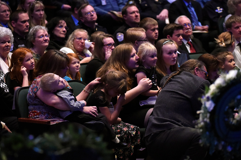 """. ARVADA, CO - MARCH 14: Family members embrace as family photos are displayed for the audience during the memorial service for Park County Deputy Corporal Nathaniel \""""Nate\"""" Carrigan at Faith Bible Chapel on March 14, 2016 in Arvada, Colorado. Carrigan was killed in the line of duty while serving a warrant in Bailey, Colorado on February 24, 2016. (Photo by Helen H. Richardson/The Denver Post)"""
