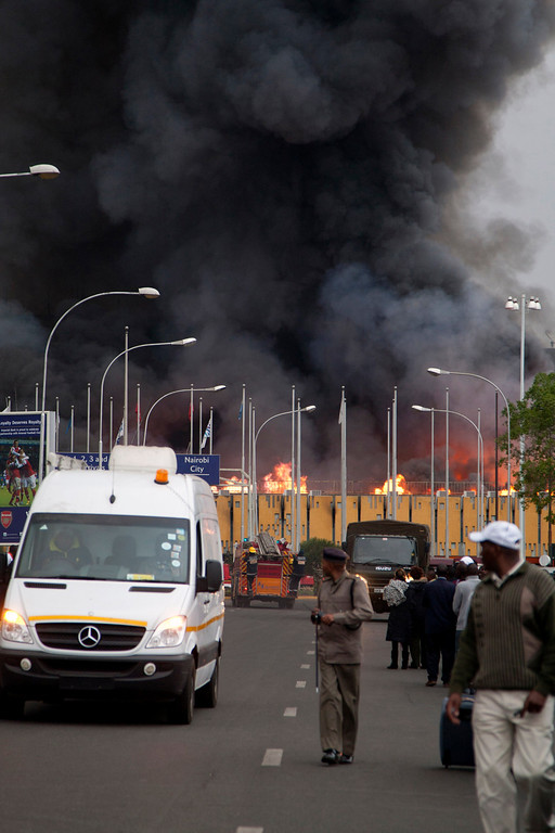 . A policeman stands guard as a fire engulfs the International arrivals hall at the Jomo Kenyatta International Airport in Nairobi, Kenya Wednesday, Aug. 7, 2013.  (AP Photo/Sayyid Azim)