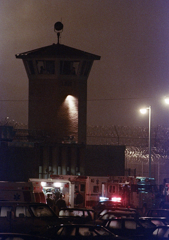 . A released hostage is loaded into an ambulance beneath a guard tower at the Southern Ohio Correctional Facility in Lucasville, Ohio, at the end of a 10-day siege. One guard and seven inmates died. (AP Photo/Bill Sikes)