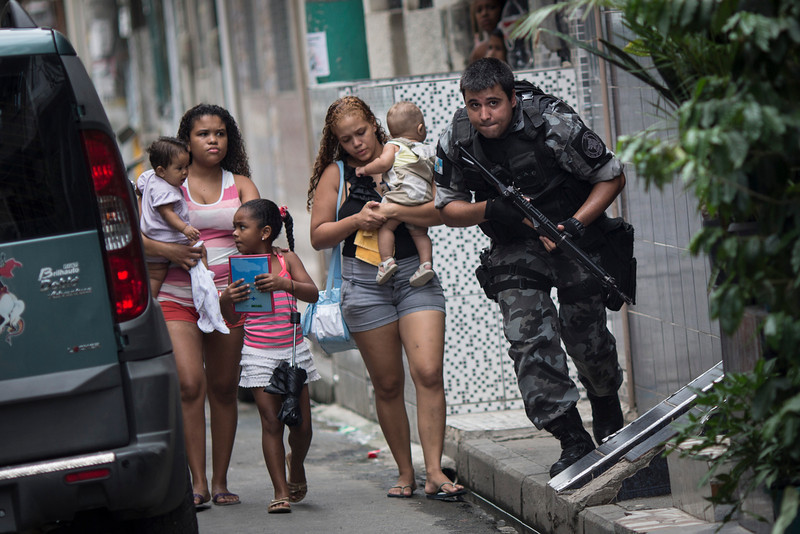 """. Upon hearing gun shots, a military police officer runs for cover, past residents, during an operation in the Mare slum complex, ahead of its \""""pacification,\"""" in Rio de Janeiro, Brazil, Tuesday, March 25, 2014. (AP Photo/Felipe Dana)"""
