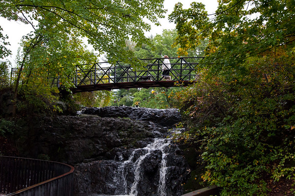10/15/18 Wesley Bunnell | Staff A dog walker crosses the bridge at Mill Pond Falls in Newington on Monday afternoon.