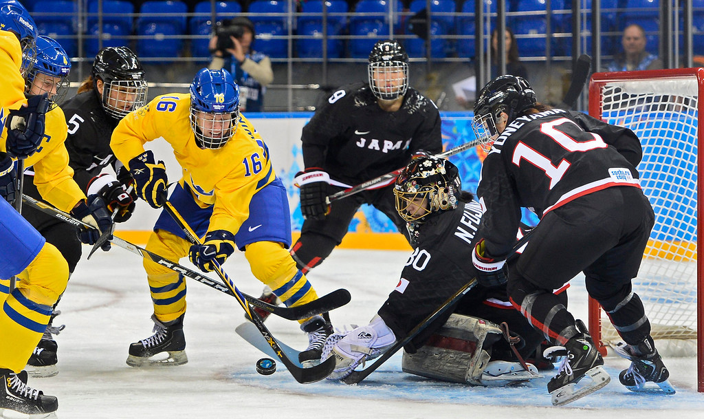 . Pernilla Winberg (CL) of Sweden fights for the puck with goalie Nana Fujimoto (CR) of Japan in the first period during the match between Sweden and Japan at the Shayba Arena in the Ice Hockey tournament at the Sochi 2014 Olympic Games, Sochi, Russia, 09 February 2014  EPA/LARRY W. SMITH