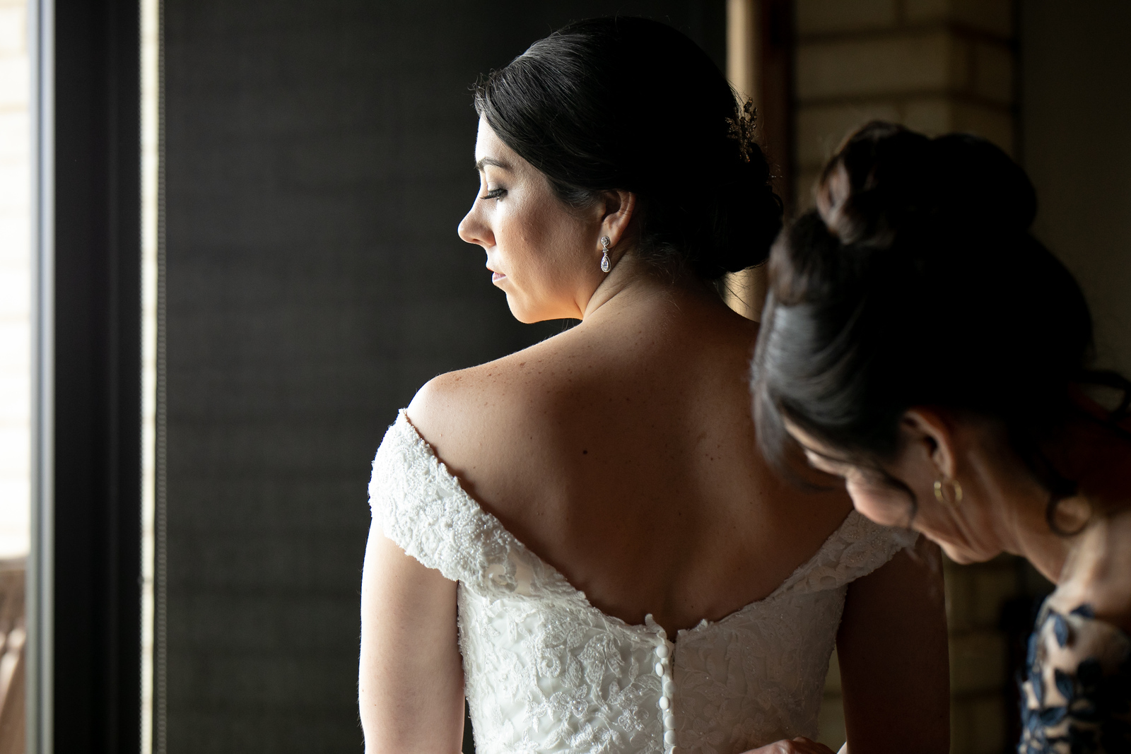 mother of the bride making final adjustments to her daughter's wedding dress