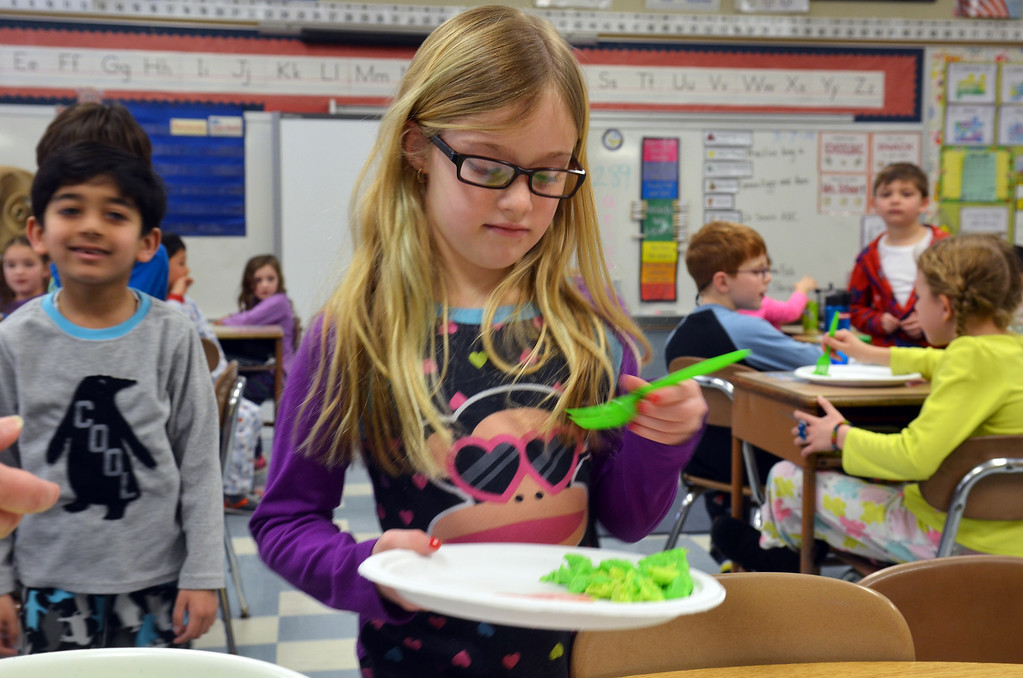 . Ava Ratcliff gets a serving of green eggs and ham.   Friday, March 7, 2014.    Photo by Geoff Patton