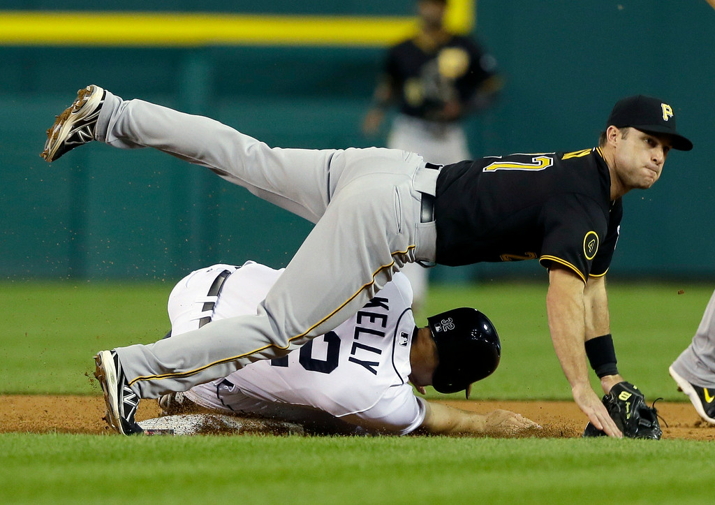 . Pittsburgh Pirates second baseman Jayson Nix falls over Detroit Tigers\' Don Kelly after throwing to first for the out on Tigers\' runner Nick Castellanos during the seventh inning of an interleague baseball game, Wednesday, Aug. 13, 2014 in Detroit. (AP Photo/Carlos Osorio)