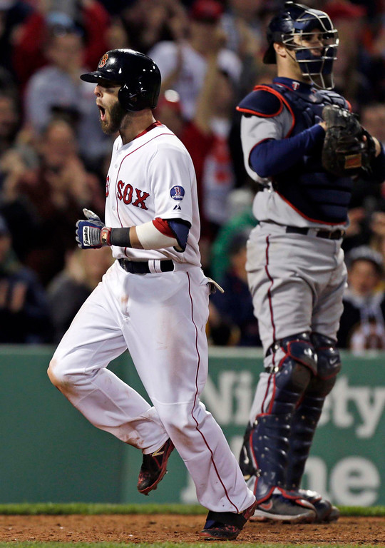 . Boston Red Sox\'s Dustin Pedroia, left, shouts as he passes Minnesota Twins catcher Joe Mauer and crosses home plate after his solo home run during the eighth inning. (AP Photo/Charles Krupa)