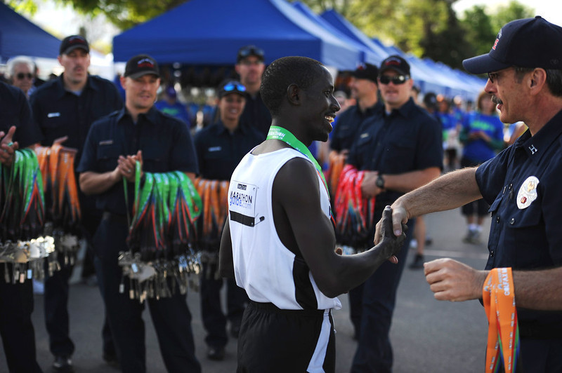 . Abraham Rutto, who just won the Colfax Marathon in a record time of 2:24:34, happily accepts the runners\' medal from West Metro firefighters after the race. The Colfax Marathon, the Half Marathon and the Urban Ten-Miler were held in City Park in Denver, CO on May 19th, 2013. The popular running events, sponsored by Kaiser Permanente, were sold out and thousands of runners took part in all three races.  Temperatures were cool with cloudy skies making for record setting times on both the marathon and the half marathon by the winners.  (Photo by Helen H. Richardson/The Denver Post)