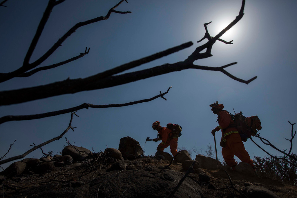 . Hand crews work on the fire line after a wildfire near Point Mugu, Calif., Saturday, May 4, 2013. On Saturday, high winds and withering hot, dry air were replaced by the normal flow of damp air off the Pacific, significantly reducing fire activity. (AP Photo/Ringo H.W. Chiu)