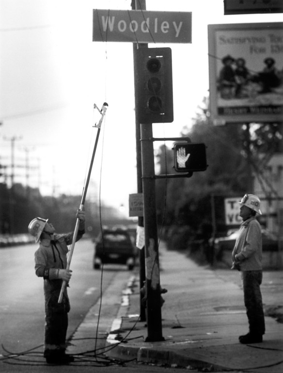 . June 28, 1992: Firefighter Phil Clark of station 90 clips downed electrical lines at the corner of Woodley and Vanowen in Van Nuys after Sunday\'s quake.  Daily News file photo