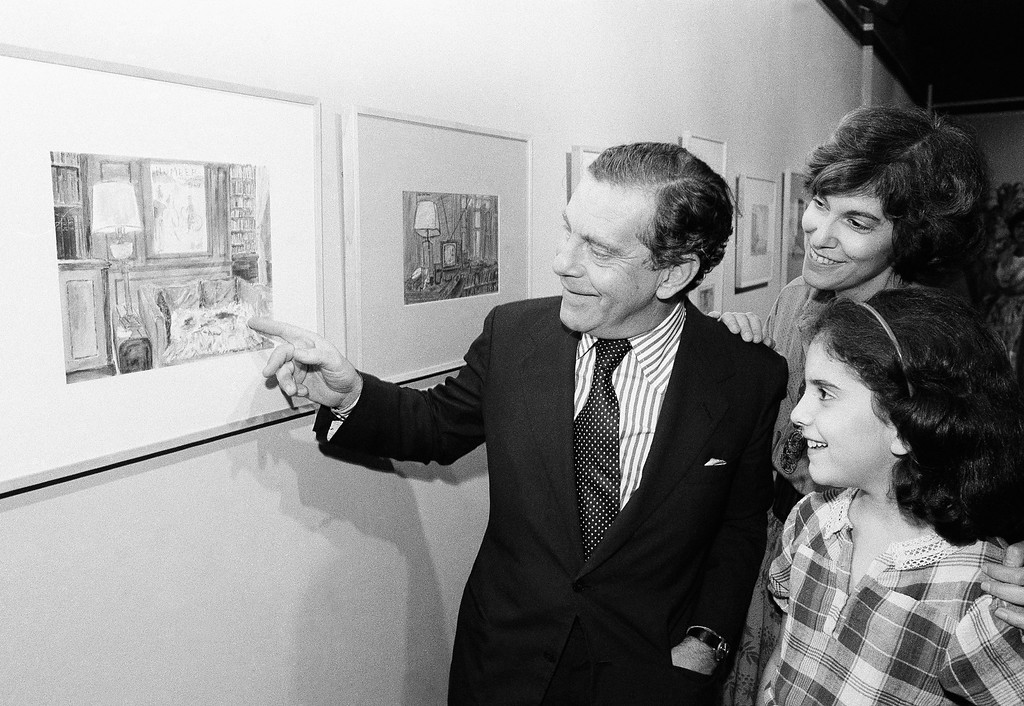 . In this Sept. 22, 1980 file photo, Morley Safer points to one of his watercolors displayed at a New York restaurant as his wife Jane and daughter Sarah look on. Safer, the veteran \'60 Minutes\' correspondent who exposed a military atrocity in Vietnam that played an early role in changing Americans view of the war, died Thursday, May 19, 2016. He was 84. (AP Photo/ Richard Drew, File)
