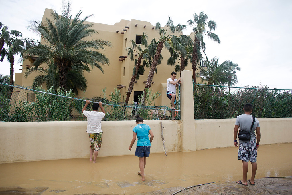 . Tourist Cesar Calzada, center, of Mexico City, climbs over a fence of the Riu resort to get out of the hotel and go search for food after Hurricane Odile severely damaged the hotel in Los Cabos, Mexico, Monday, Sept. 15, 2014.  (AP Photo/Victor R. Caivano)