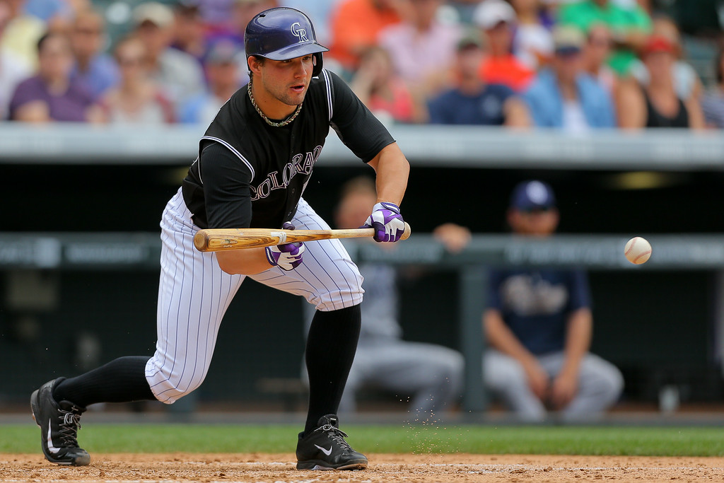 . DENVER, CO - JULY 9:  Relief pitcher Tommy Kahnle #54 of the Colorado Rockies lays down a sacrifice bunt during the fifth inning against the San Diego Padres at Coors Field on July 9, 2014 in Denver, Colorado. (Photo by Justin Edmonds/Getty Images)