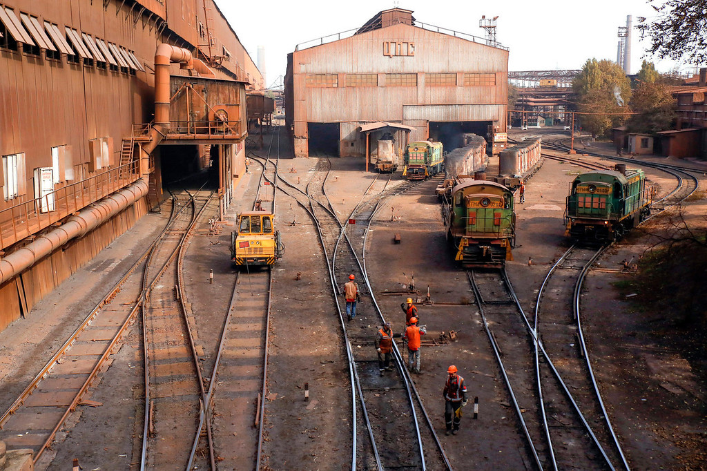 . Employees walk across railway tracks and past train locomotives inside the Zaporizhstal steel plant, owned and operated by Metinvest BV, at their site in Zaporizhzhya, Ukraine, on Monday, Oct. 14, 2013. Metinvest BV, Ukraine\'s largest steelmaker, last year acquired 49.9% in steelmaker Zaporizhstal a manufacturer of semi-finished steel products, including hot and cold-rolled plates and coils. Photographer: Vincent Mundy/Bloomberg