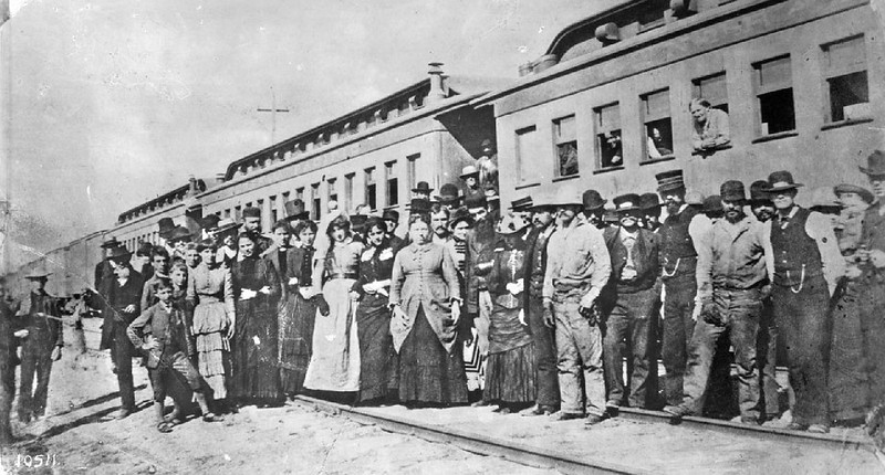 "Newly arrived passengers posing in front of their Southern Pacific train during the ""Boom Days"", ca.1885"