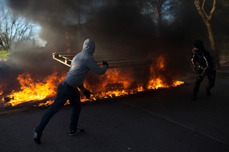 . A student sets fire and makes barricades during the first day of student strike to protest a government education reform and cutbacks in grants and staffing, at Complutense University in Madrid, Spain, Wednesday, March 26, 2014. Spanish police say they arrested more than 50 students when the police moved in to end the occupation of a campus building after the university had asked them to intervene. Students, many with their faces covered, set fire to trash containers and set up barricades on at least two streets in the university complex during the protest. (AP Photo/Andres Kudacki)