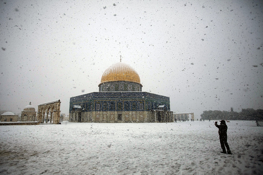 Description of . A man takes pictures of the snow-covered Dome of the Rock at the Al-Aqsa mosque compound in the old city of Jerusalem on January 10, 2013. Jerusalem was transformed into a winter wonderland after heavy overnight snowfall turned the Holy City and much of the region white, bringing hordes of excited children onto the streets. AHMAD GHARABLI/AFP/Getty Images