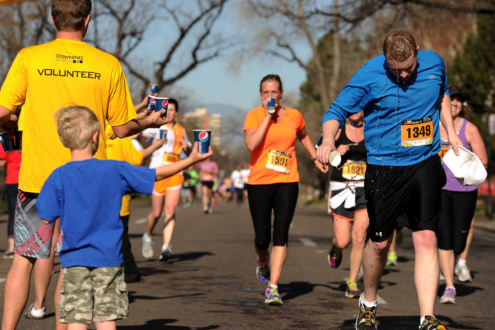 . Luke Zonca, 6, helps hand out water to runners taking part in the 10 mile run.  The 31st annual Cherry Creek Sneak had all sorts of distances for this year\'s race.  The Sneak, as it is affectionately named, had a 10 mile, 5 mile, 3.1 mile or 5K, a 1.5 mile Denver\'s 7 Sprint, and a kid\'s fun run for thousands of competitors, runners and walkers that turned out in the Cherry Creek neighborhood of Denver, CO on April 28, 2013.  The race is always held the last Sunday in April. This year participants cheered the national anthem and observed a moment of silence for victims of the Boston Marathon bombing at the start of each race. (Photo by Helen H. Richardson/The Denver Post)