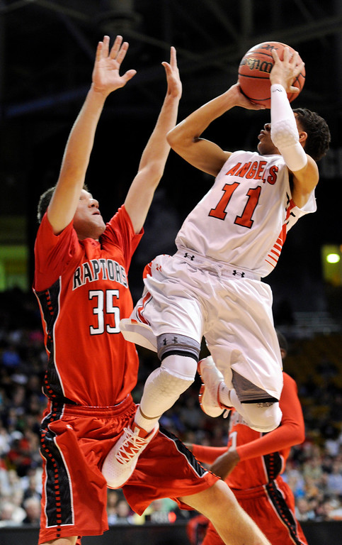 . BOULDER, CO. - MARCH 16: Angels guard Brian Carey (11) looked for a way past Raptors defender Blend Avdili (35) in the second half. The Eaglecrest High School boy\'s basketball beat Denver East 63-44 in the 5A championship game Saturday, March 16, 2013 at the Coors Events Center in Boulder.  (Photo By Karl Gehring/The Denver Post)