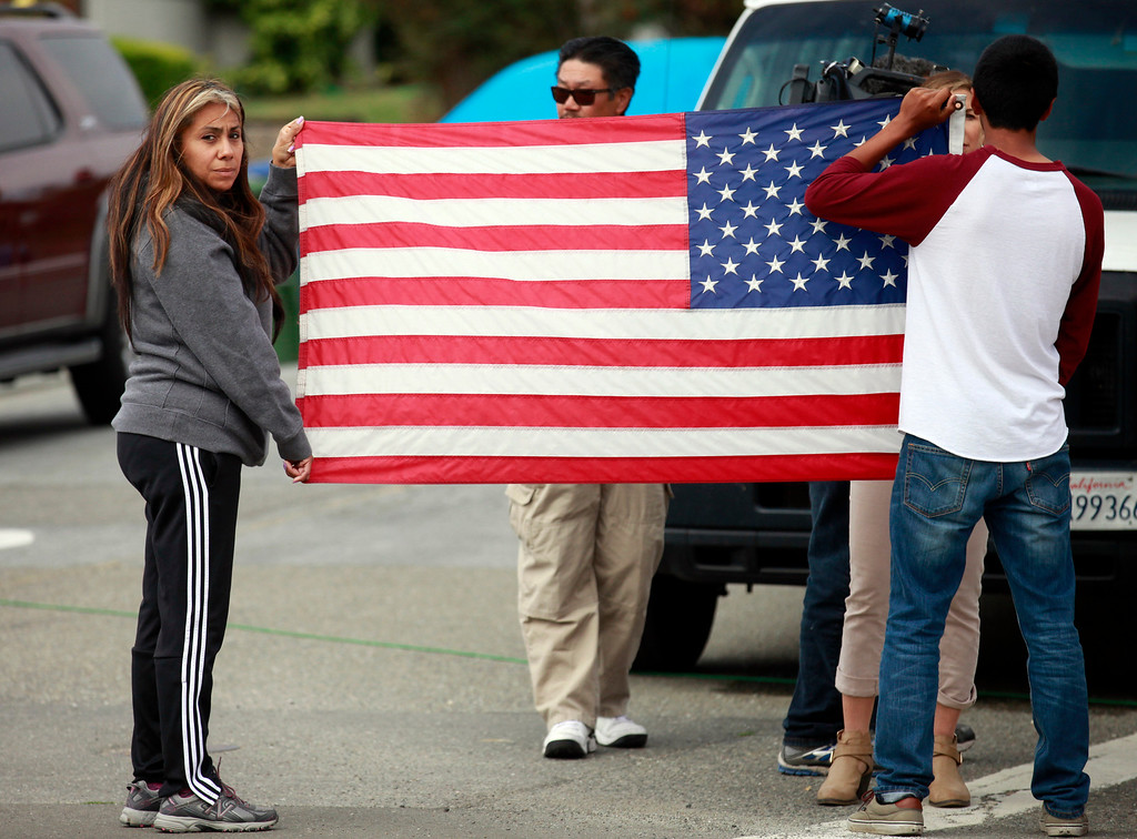 . Ophelia Ramirez and her son Carlos Ramirez, 16, hold an American flag up as the procession of Hayward police escorts the Alameda County Coroner\'s van carrying their fellow officer Sergeant Scott Lunger leaves Eden Medical Center in Castro Valley, Calif., on Wednesday, July 22, 2015.  Lunger was shot and killed during a traffic stop early Wednesday morning. (Laura A. Oda/Bay Area News Group)