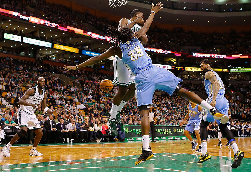 . BOSTON, MA - FEBRUARY 10: Jeff Green #8 of the Boston Celtics and Kenneth Faried #35 of the Denver Nuggets collide in midair underneath the basket during the game on February 10, 2013 at TD Garden in Boston, Massachusetts.  (Photo by Jared Wickerham/Getty Images)