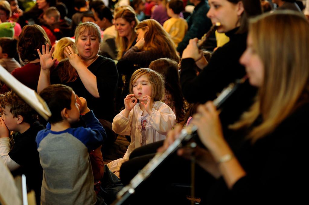 . In her pajamas, Annie Wheeler, 5, of the Early Childhood Center plays an imaginary flute with members of the Junior Symphony Guild at the Inside the Orchestra for Tiny Tots performance at Temple Emanuel in Denver, Colorado on Thursday, February 9,  2012. Joe Amon, The Denver Post