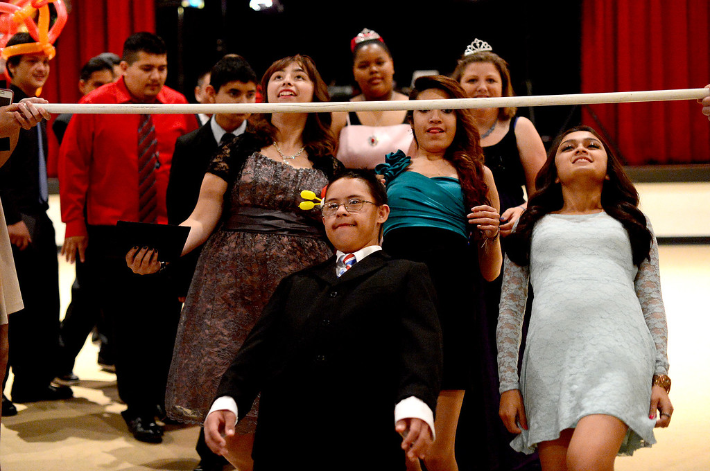 . Students do the limbo dance during Glendora High School\'s Best Buddies Prom for high school students with special needs Friday night, April 19, 2013 at the Glendora campus. (SGVN/Staff Photo by Sarah Reingewirtz)