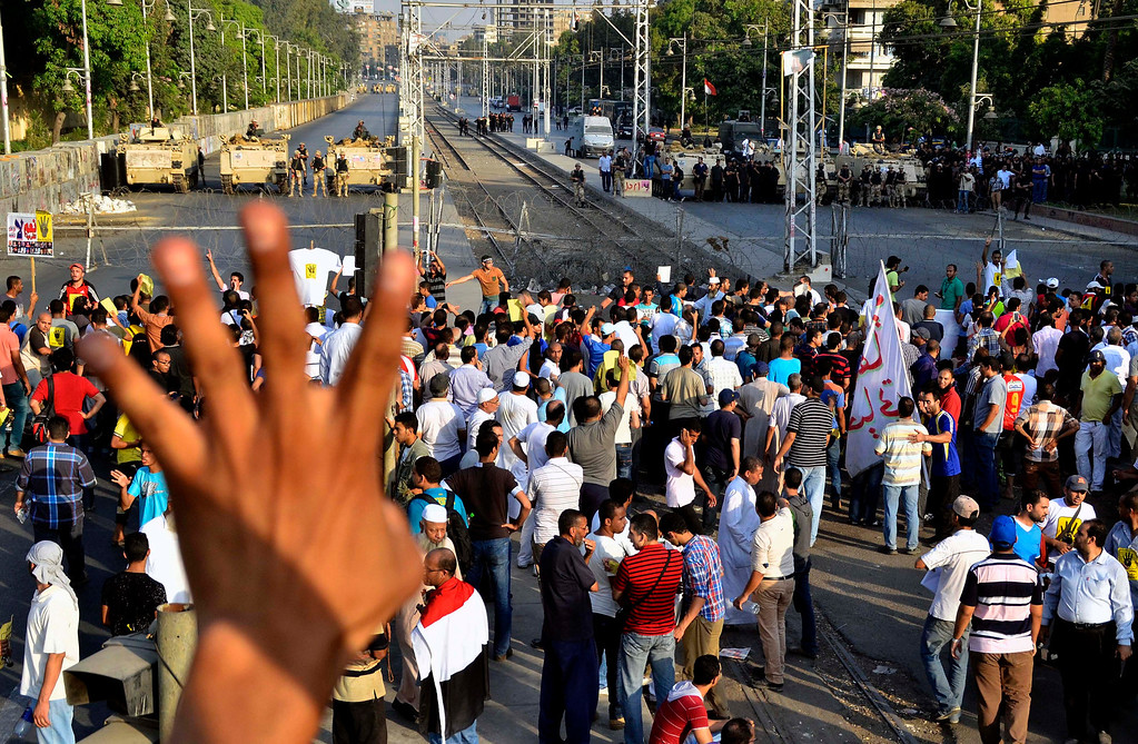 . Supporters of Egypt\'s ousted President Mohammed Morsi gather outside the presidential palace as soldiers and armored personnel carriers block a road in Cairo, Friday, Aug. 30, 2013. One supporter holds out four raised fingers, which has become a symbol of the Rabaah al-Adawiya mosque, where Morsi supporters had held a sit-in for weeks that was violently dispersed on Aug. 14, resulting in the deaths of hundreds. Tens of thousands of protesters and Muslim Brotherhood supporters rallied Friday throughout Egypt against a military coup and a bloody security crackdown, though tanks and armored police vehicles barred them from converging in major squares. (AP Photo/Mostafa Darwish)