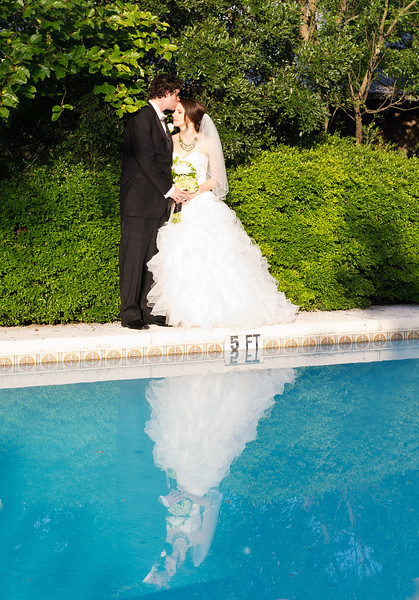 Bride and groom's reflection in pool