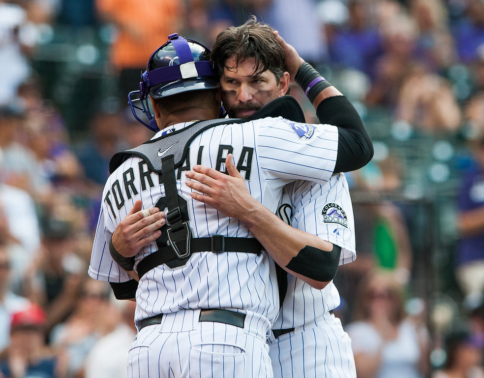 . Yorvit Torrealba #8 congratulates Todd Helton #17 of the Colorado Rockies on his 2,500th career hit after the seventh inning of a game against the Cincinnati Reds at Coors Field on September 1, 2013 in Denver, Colorado. (Photo by Dustin Bradford/Getty Images)
