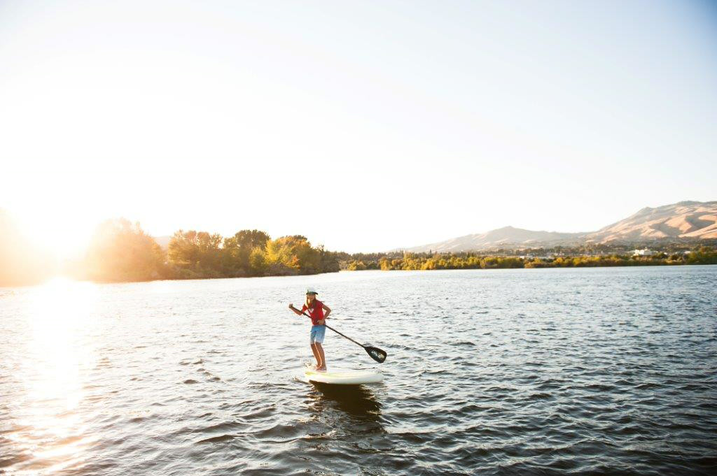 . A stand-up paddle boarder glides across the Columbia River in Wenatchee, Washington. (Photo provided by Shane Wilder for the Wenatchee Chamber of Commerce)