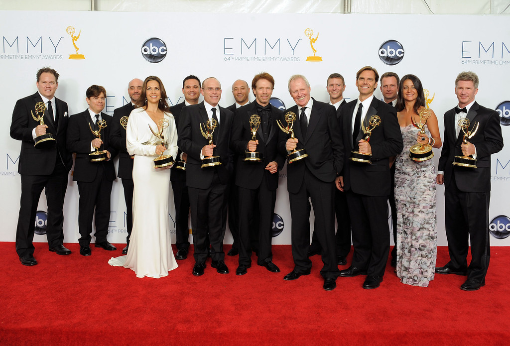 ". Producer Jerry Bruckheimer, center, winner Outstanding Reality-Competition Program for ""The Amazing Race\"", poses backstage at the 64th Primetime Emmy Awards at the Nokia Theatre on Sunday, Sept. 23, 2012, in Los Angeles. (Photo by Jordan Strauss/Invision/AP)"