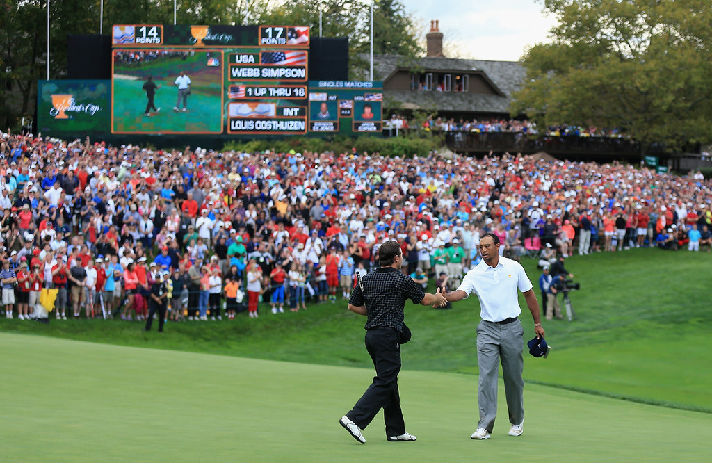 . Tiger Woods of the U.S. Team (R) shakes hands with Richard Sterne of South Africa and the International Team on the 18th green after Woods 1up victory won the Cup for the U.S.Team during the Day Four Singles Matches at the Muirfield Village Golf Club on October 6, 2013  in Dublin, Ohio.  (Photo by David Cannon/Getty Images)