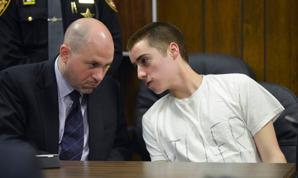. Defense attorney Ian Friedman, left, talks with T.J. Lane during sentencing Tuesday, March 19, 2013, in Chardon, Ohio. Lane, was given three lifetime prison sentences without the possibility of parole on Tuesday for opening fire last year in a high school cafeteria in a rampage that left three students dead and three others wounded. Lane, 18, had pleaded guilty last month to shooting at students in February 2012 at Chardon High School, east of Cleveland.  (AP Photo/The News-Herald, Duncan Scott, Pool)