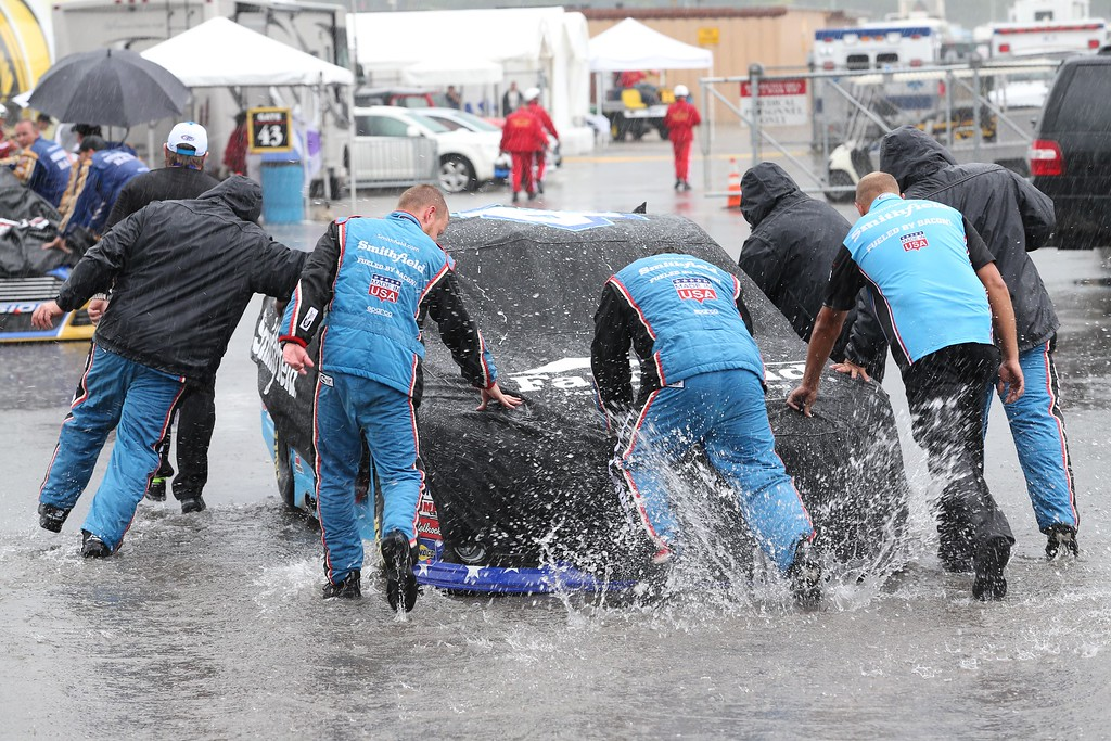 . Crew member for Aric Almirola push his car back to the garage during a rain delay at the NASCAR Sprint Cup series auto race at Michigan International Speedway, Sunday, June 14, 2015, in Brooklyn, Mich. (AP Photo/Dave Frechette)